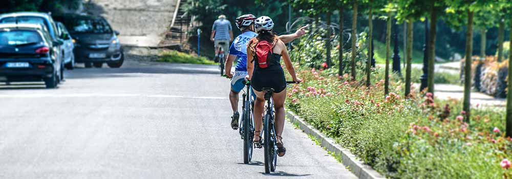 Two cyclists riding their bikes on the road